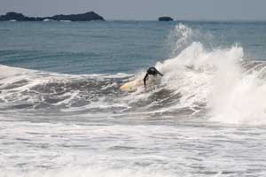 Surfer in the waves of Playa Jaco. Located on the central Pacific coast of Costa Rica, in relatively close proximity to the airport and San Jose..