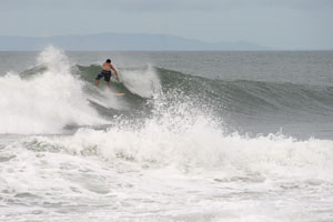 A surfer catching a left-hander, in the back the Nicoya Peninsula is visible.