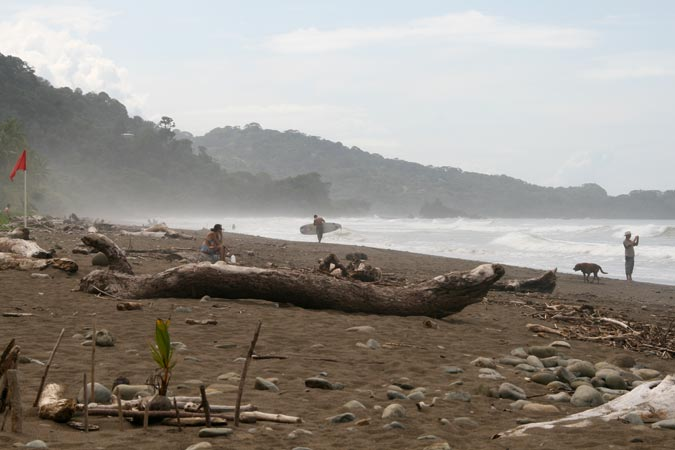 Dominical Beach covered with stones and driftwood.