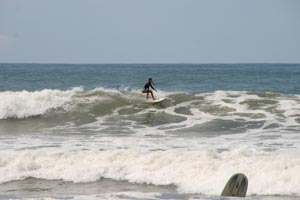 A surfer girl surfing a nice wave at Dominical.