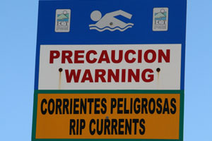 Signs posted along the beach warn swimmers about rip currents.